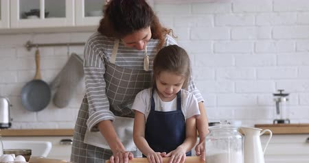 домохозяйка : Happy young mommy helping little preschool daughter using rolling pin, preparing dough for homemade pastry together in modern kitchen. Smiling small kid girl enjoying cooking baking with mom. Стоковые видеозаписи