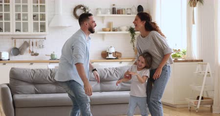 Happy young man joking with attractive wife, having fun together with small kids in modern kitchen interior room. Overjoyed millennial couple playing dancing with laughing little children siblings.