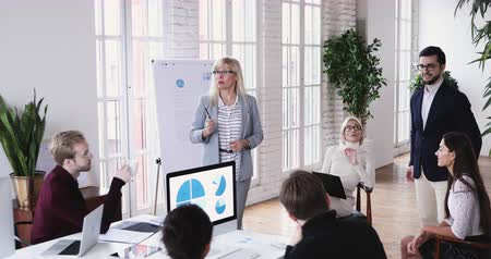 Confident middle aged business woman executive manager director giving instructions leading corporate group briefing training team people presenting project to staff employees during group meeting