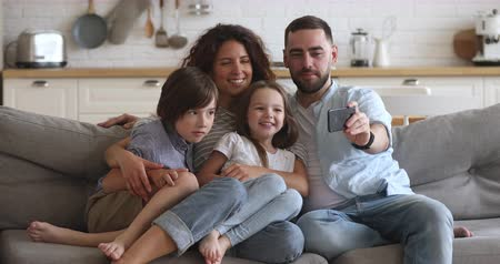 milující : Happy bonding family of four sitting on couch, smiling father holding mobile phone, taking selfie. Excited couple posing for photo with children siblings or holding online call with grandparents.