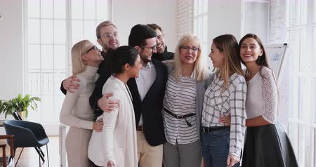 гордый : Proud older mature female leader boss unite young employees hugging laughing in office, happy friendly business people hugging bonding having fun standing together building successful team concept Стоковые видеозаписи