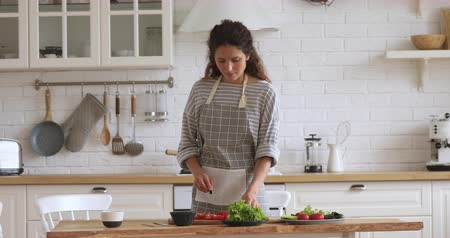 Pleasant young attractive woman chopping fresh vegetables for salad on wooden board alone in modern kitchen. Smiling caucasian housewife enjoying cooking, preparing healthy vegetarian meal for dinner. Stock Footage
