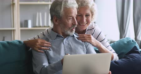 ailelerin : Happy elderly woman peeking from husband shoulder, looking at computer screen. Excited middle aged man explaining new laptop software, enjoying free leisure weekend time together in living room. Stok Video