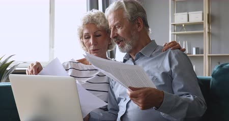 dokumentum : Smiling older retired couple holding computer and financial paper documents, checking domestic bills, discussing expenses together at home. Happy middle aged clients planning bank loan credit.