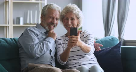 Happy middle aged family spouses having fun, making selfie photos together on smartphone at home. Laughing bonding mature older married couple using funny mobile applications or recording video.