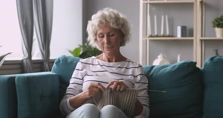 wełna : Peaceful middle aged retired hoary woman knitting woolen scarf sweater, relaxing on cozy couch alone at home. Calm mature older grandmother holding knitting needles, enjoying hobby in living room. Wideo