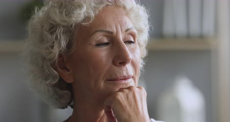 Head shot close up middle aged dreamy woman looking away, thinking planning future, remembering good life moments. Lost in thoughts mature older female pensioner visualizing dreams alone at home.