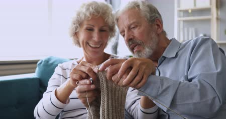 sedmdesátá léta : Head shot happy loving middle aged married couple having fun together, knitting handmade grey woolen scarf. Bonding affectionate smiling spouses enjoying funny hobby together, sitting on sofa.
