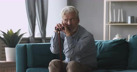 elliler : Thoughtful tired middle aged man sitting on couch relying on walking stick, feeling stressed. Depressed mature grandfather thinking of geriatric health problems disease, suffering from loneliness. Stok Video