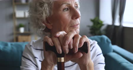 sedmdesátá léta : Focus on older hoary woman holding hands on walking stick. Head shot close up thoughtful disabled female pensioner looking away, relying on cane, thinking of health or mental problems alone at home. Dostupné videozáznamy