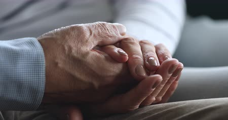 Close up elderly woman holding wrinkled hand of retired old husband, showing support love. Caring older family couple enjoying tender moment, having trustful conversation or comforting each other.