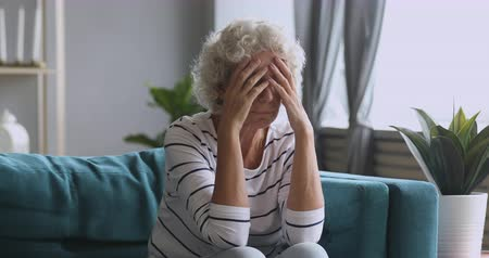 Frustrated mature woman sitting on sofa, suffering from terrible head ache alone at home. Stressed middle aged pensioner suffering from high blood pressure, holding head in hands, feeling desperate. Vídeos