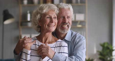 Happy mature man husband embracing smiling middle aged wife, looking at camera. Bonding attractive older senior family couple looking away, dreaming of future, planning retirement together at home.