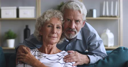 objetí : Head shot video portrait loving elderly husband embracing sitting on couch smiling hoary woman, looking at camera. Happy married couple posing for family portrait, enjoying tender moment together.