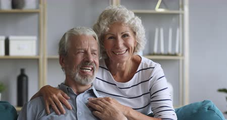 sedmdesátá léta : Overjoyed middle aged family couple embracing relaxing on comfortable sofa, looking at camera. Positive happy loving older spouses enjoying sweet tender moment together, posing for photo at home. Dostupné videozáznamy