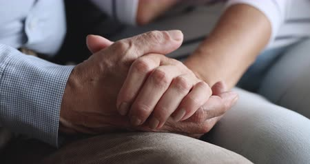 dialog : Close up older loving man holding wrinkled hand of trustful wife. Bonding family couple joining hands, showing love care. Affectionate spouses enjoying sweet tender moment, supporting each other. Wideo