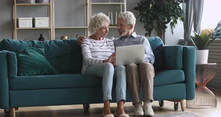 sedmdesátá léta : Full length happy older family couple relaxing on comfortable couch at home, using computer. Smiling middle aged married retired spouses web surfing, discussing news, shopping online together.