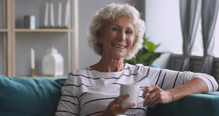 Head shot video portrait happy older grandmother resting on cozy sofa, holding mug with hot beverage. Smiling middle aged female pensioner enjoying free leisure morning time alone in living room.