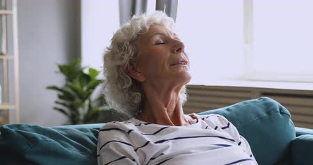 Head shot peaceful mature retired woman breathing fresh air full breasts, relaxing on comfortable sofa alone at home. Mindful happy middle aged tranquil grandmother enjoying break pause leisure time.