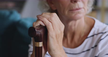 fraco : Close up upset middle aged grandma holding hands on cane, feeling loneliness at home. Stressed disabled mature retired woman suffering from geriatric health problems, sitting alone in living room.