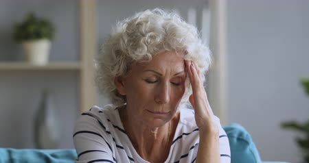 отчаянный : Head shot close up exhausted middle aged hoary woman massaging temples, suffering from painful feelings, migraine alone at home. Tired mature older female pensioner having headache, mental stress. Стоковые видеозаписи