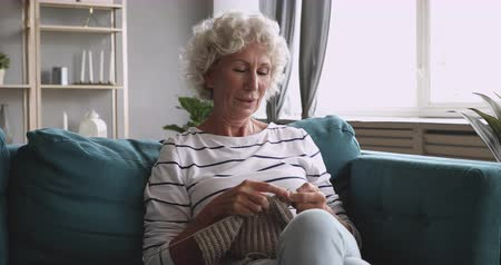 sedmdesátá léta : Happy elderly senior woman knitting handmade clothes, enjoying leisure free time at home. Smiling middle aged grandmother relaxing on comfortable sofa, doing handicraft, sitting alone in living room. Dostupné videozáznamy