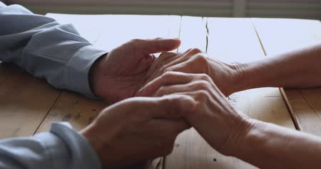 sedmdesátá léta : Mature retired family couple holding hands together on table, showing care. Loving bonding spouses grandparents supporting each other, sharing problems, overcoming troubles together, close up view. Dostupné videozáznamy
