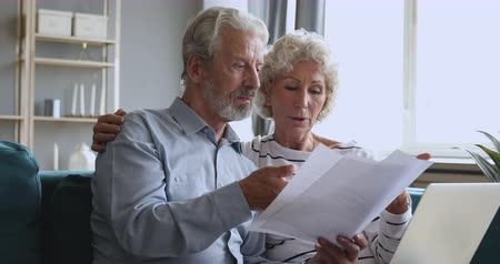 měsíčně : Focused older man holding paper financial documents, discussing monthly expenses at home with wife. Concentrated middle aged family couple worrying about payments, checking domestic bills together.