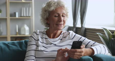 Happy middle aged woman holding smartphone, using mobile applications. Smiling senior elderly female pensioner communicating with friends online via cellphone, shopping web surfing alone at home.