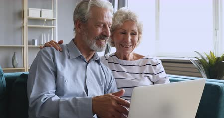 abraços : Smiling 60s woman cuddling pleasant husband, explaining computer software. Happy middle aged married couple resting on comfortable couch, discussing pc applications, media news together at home.