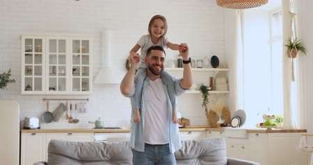 milující : Smiling young daddy carrying excited little daughter, giving piggyback ride, dancing, having fun together. Happy small kid girl sitting on fathers shoulders, involved in funny activity at home.