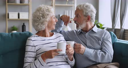 Affectionate mature family couple relaxing on cozy sofa, enjoying pleasant conversation, holding cups of hot tea. Loving happy middle aged man joking talking discussing with elderly smiling wife. Vídeos