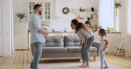 ailelerin : Happy carefree couple dancing together with two little children in modern kitchen room. Overjoyed spouses having fun joking with small kids siblings, enjoying funny activity laughing bonding at home. Stok Video