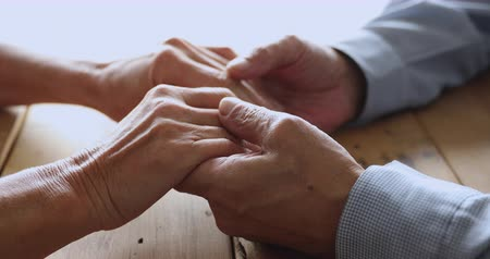 overcoming : Romantic middle aged married couple stroking hands of each other on table giving support to each other. Loving bonding elderly mature family spouses enjoying sincere trustful conversation at home.