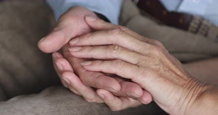 Empathic older family couple stroking hands of each other, showing love care hope, close up. Bonding middle aged spouses enjoying tender moment together, two loving grandparents understanding concept.