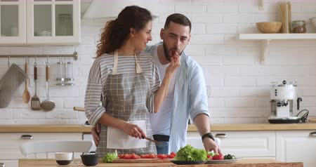 objetí : Young handsome man cuddling from back smiling attractive wife in apron preparing healthy vegetarian dish for romantic dinner. Joyful millennial woman feeding loving husband while cooking in kitchen.