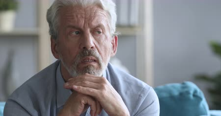 elliler : Head shot worried older mature man sitting on couch, suffering from depression psychological problem alone at home. Frustrated grandpa trying remembering important information, dementia disease.