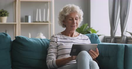 lezing : Pleasant smiling elderly mature woman resting on sofa, using digital tablet alone at home. Happy older pensioner web surfing information, chatting on social networks, studying or shopping online.