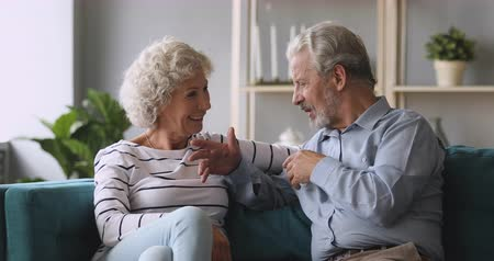 söylemek : Smiling middle aged hoary woman listening to emotional mature husband, communicating at home. Engaged in interesting conversation older married family couple relaxing together on cozy couch.