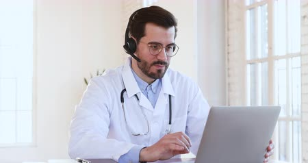 konferencja : Friendly smiling professional male medic doctor wear headset make conference video call on laptop consult patient look at camera show thumbs up recommend telemedicine online chat service app concept Wideo