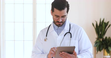 záznamy : Male professional doctor physician wear white uniform stethoscope holding using digital tablet pad computer applications modern medical healthcare technology device concept stand in hospital office