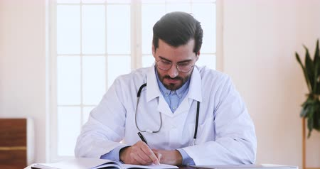 prescribe : Focused male professional medic doctor general practitioner physician wear white coat glasses writing notes making patients appointments schedule in notepad sitting at work desk in medical office Stock Footage