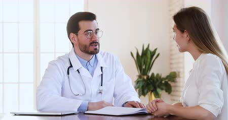 terapeuta : Smiling professional male doctor physician or plastic surgeon and happy young adult woman patient client handshake during medical consultation making agreement express gratitude and trust concept