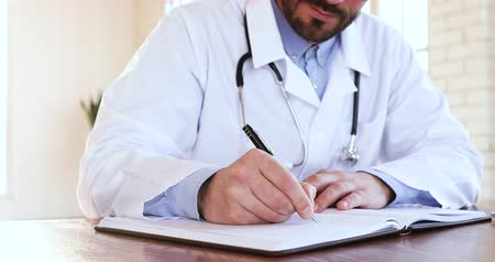 gyógyszerész : Male gp doctor wear white coat holding pen write prescription in notebook, man professional medic general practitioner physician make notes in paper notepad planning work day sit at desk, close up view Stock mozgókép