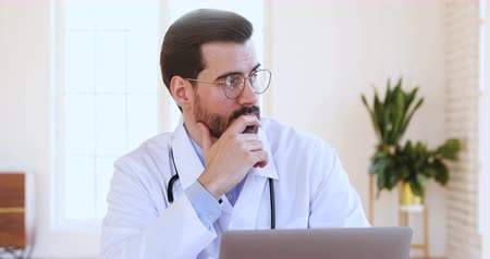 stethoskop : Serious thoughtful male professional doctor wear white coat glasses using laptop working on computer looking away thinking of medical problem solution making decision doing medical research concept