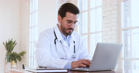 webseite : Male professional medic doctor wear medical coat using notebook computer, man general practitioner physician working on laptop technology in hospital check digital data chatting with patient concept Videos