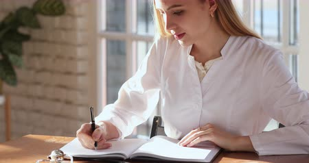 dokumentum : Young woman professional medic doctor nurse practitioner wear white coat writing patient information records notes prescription in paper notebook doing paperwork sit at desk workplace in hospital