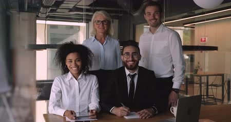 etnia africano : Happy different generations business people posing for photo in modern office. Smiling older and younger confident mixed race team of professionals executives standing together, looking at camera.