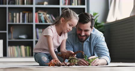 zabawka : Smiling adult daddy and cute small kid daughter having fun playing dinosaurs toys spend leisure time together at home, happy single father enjoy funny game with little preschooler child girl on floor