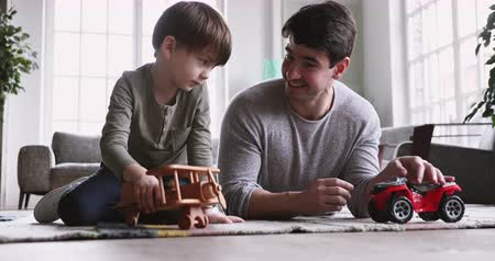 zabawka : Young father and cute small kid son playing funny racing game relax on carpet floor at home, happy male family adult dad and little child boy having fun with toy car plane engaged in leisure activity